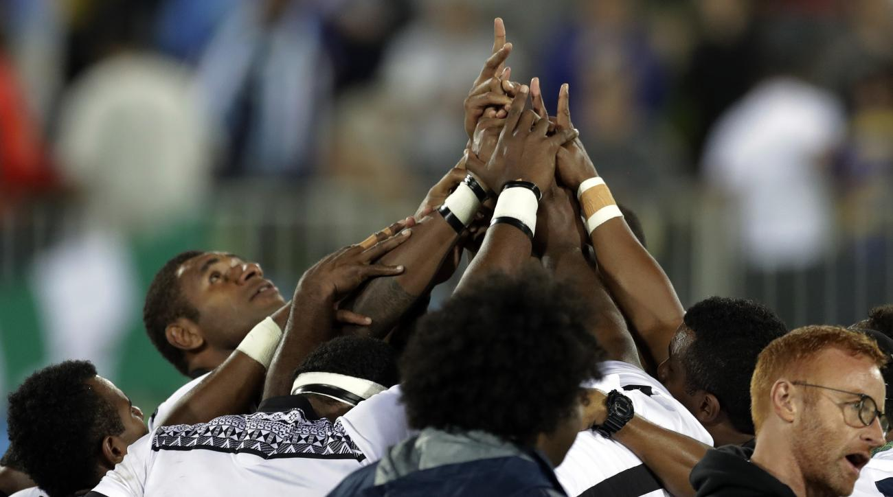 Fiji's players form a human ring after winning the men's rugby sevens gold medal match against Britain at the Summer Olympics in Rio de Janeiro, Brazil, Thursday, Aug. 11, 2016. (AP Photo/Themba Hadebe)