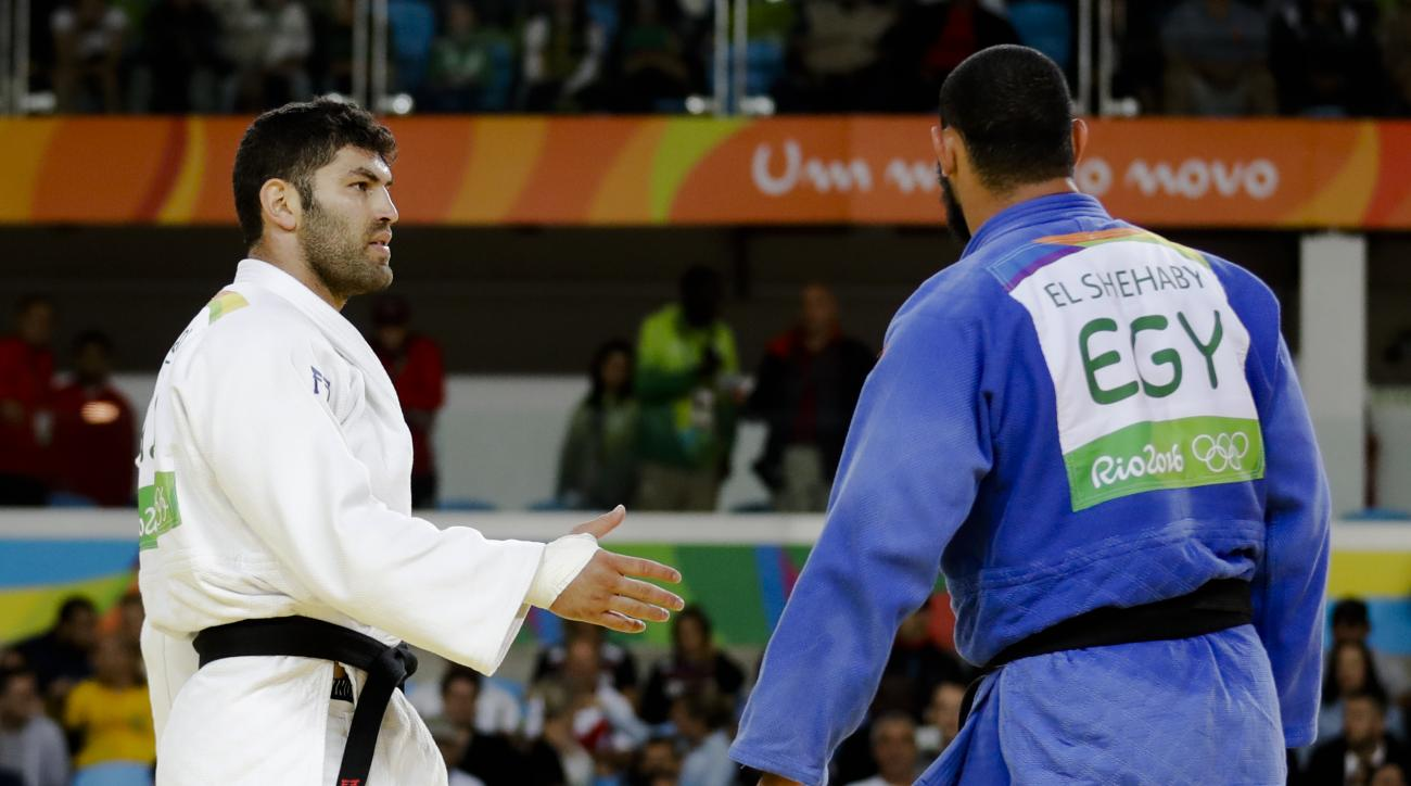 Egypt's Islam El Shehaby, blue, declines to shake hands with Israel's Or Sasson, white, after losing during the men's over 100-kg judo competition at the 2016 Summer Olympics in Rio de Janeiro, Brazil, Friday, Aug. 12, 2016. (AP Photo/Markus Schreiber)