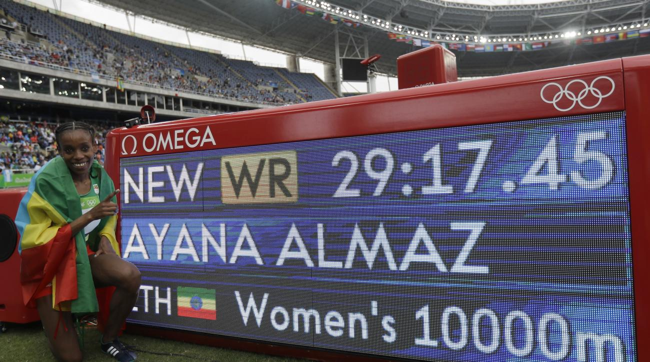 Ethiopia's Almaz Ayana poses next to a scoreboard showing her new world record in the women's 10,000-meter final during the Summer Olympics in Rio de Janeiro, Brazil, Friday, Aug. 12, 2016. (AP Photo/Matt Slocum)