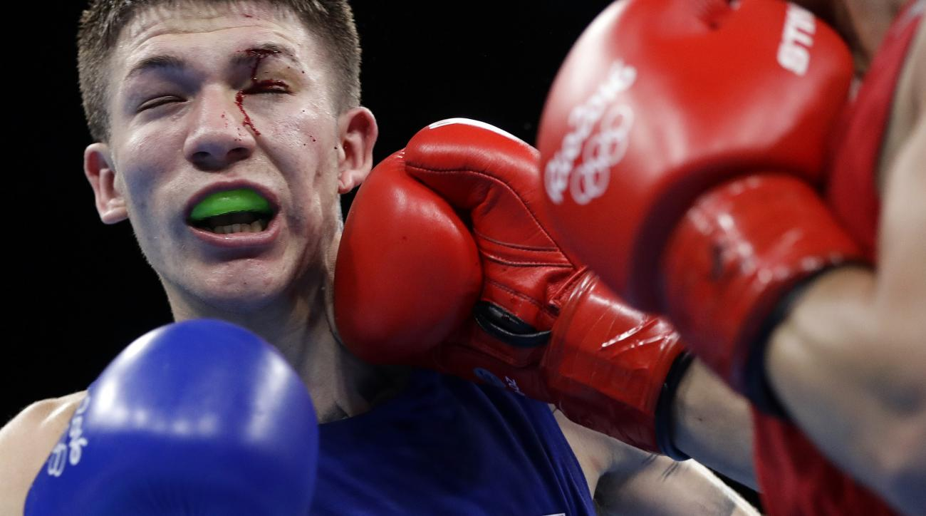 United State's Nico Miguel Hernandez, left, gets punched as he fights Uzbekistan's Hasanboy Dusmatov during a men's light flyweight 49-kg semifinals boxing match at the 2016 Summer Olympics in Rio de Janeiro, Brazil, Friday, Aug. 12, 2016. (AP Photo/Frank