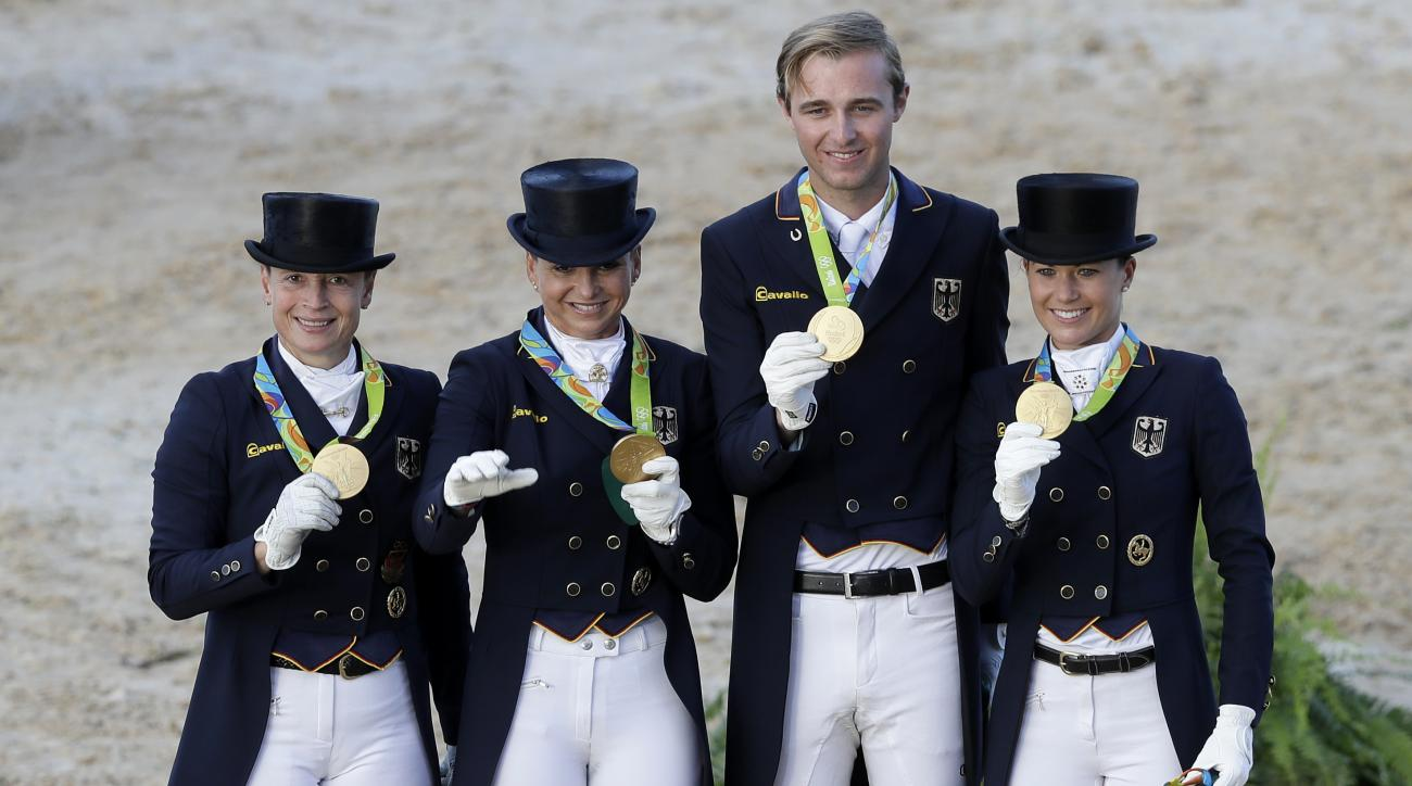 Gold medal winners Germany's Isabell Werth, left, Dorothee Schneider, second left, Sonke Rothenberger, second right, and Kristina Broring-Sprehe, right, after winning the team dressage equestrian competition at the 2016 Summer Olympics in Rio de Janeiro,