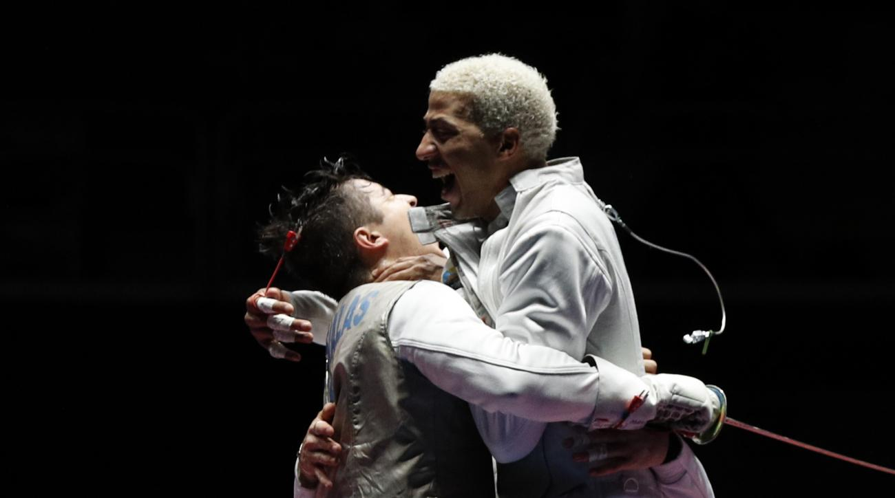 Alexander Massialas from United States, left, celebrates with Miles Chamley-Watson from United States, after defeating Italy team in the men's team foil competition at the 2016 Summer Olympics in Rio de Janeiro, Brazil, Friday, Aug. 12, 2016. (AP Photo/Vi