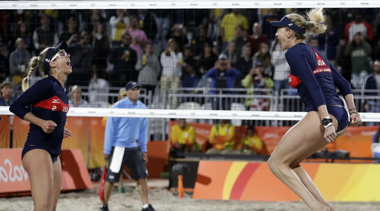 United States' Kerri Walsh Jennings, right, celebrates a win over Italy with teammate April Ross during a women's beach volleyball round of 16 match at the 2016 Summer Olympics in Rio de Janeiro, Brazil, Saturday, Aug. 13, 2016. (AP Photo/Marcio Jose Sanc