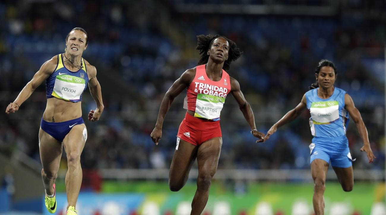 Trinidad and Tobago's Kelly-Ann Baptiste, center, India's Dutee Chand, right, and Ukraine's Olesya Povkh compete in a women's 100-meter heat during the athletics competitions of the 2016 Summer Olympics at the Olympic stadium in Rio de Janeiro, Brazil, Fr
