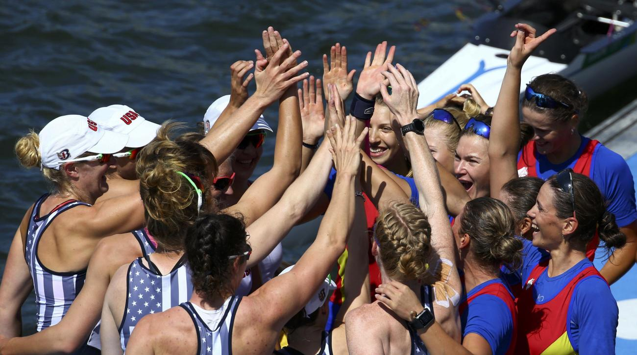The women's rowing teams from the United States, left, and Romania celebrate on the dock after winning medals in the women's eight event at Lagoa in Rio de Janeiro, Brazil, Saturday, Aug. 13, 2016. Romania took the bronze, the United states the gold and B