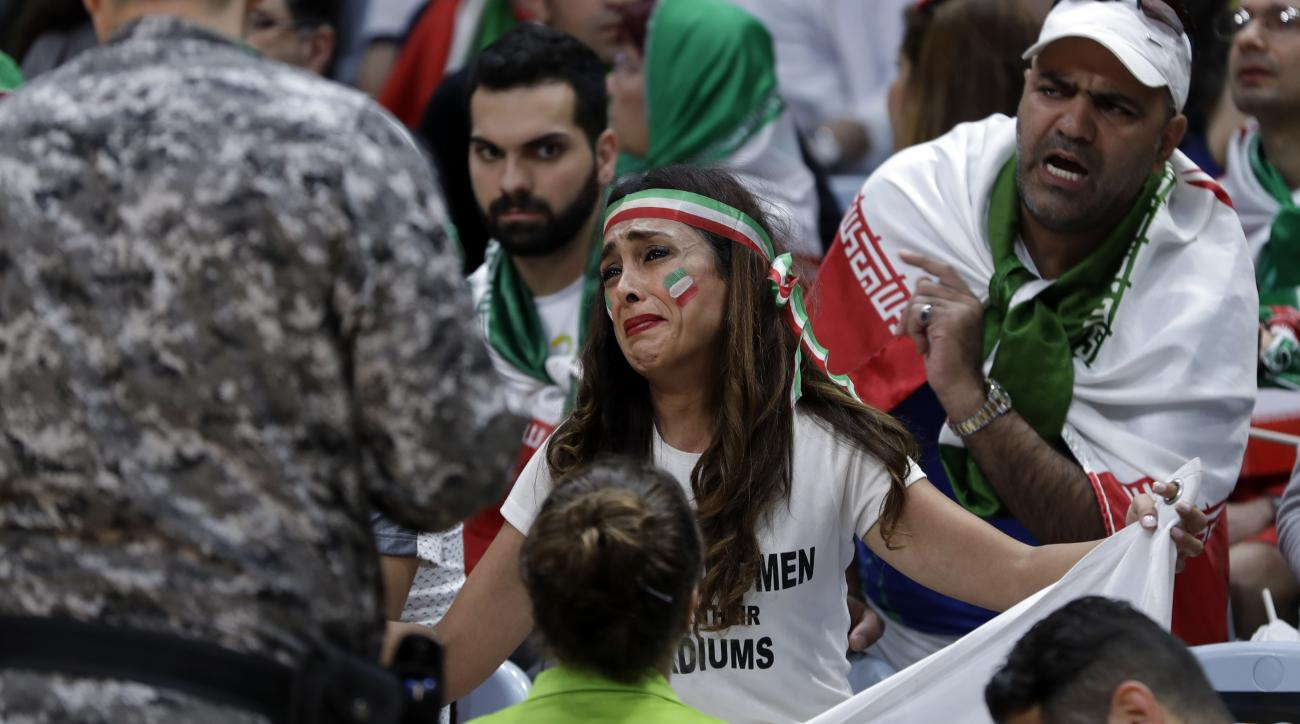 Sarai Darya pleads with workers and security personnel as they consider removing her for holding up a large sign protesting the fact that women have not been allowed to attend volleyball matches in Iran, during a men's preliminary volleyball match between