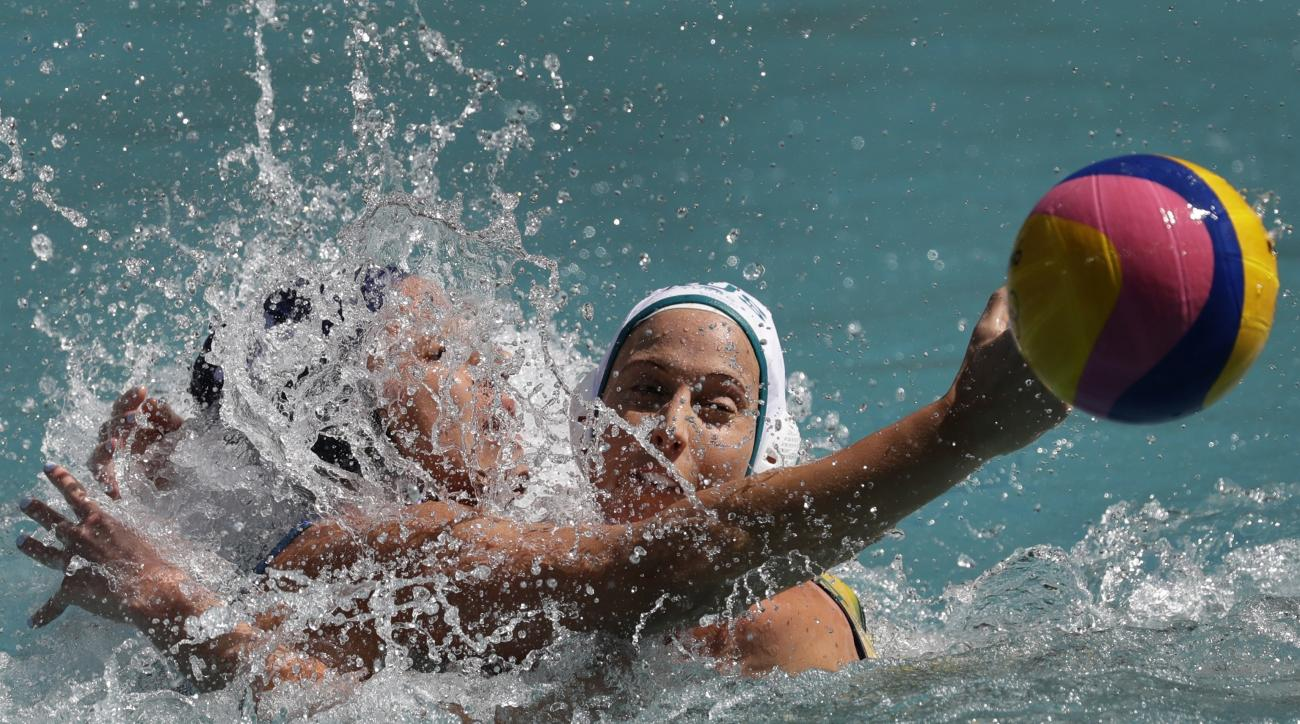 Brazil's Gabriela Mantellato, left, passes the ball forward as Australia's Glencora McGhie goes to block during their women's water polo preliminary round match at the 2016 Summer Olympics in Rio de Janeiro, Brazil, Saturday, Aug. 13, 2016. (AP Photo/Serg