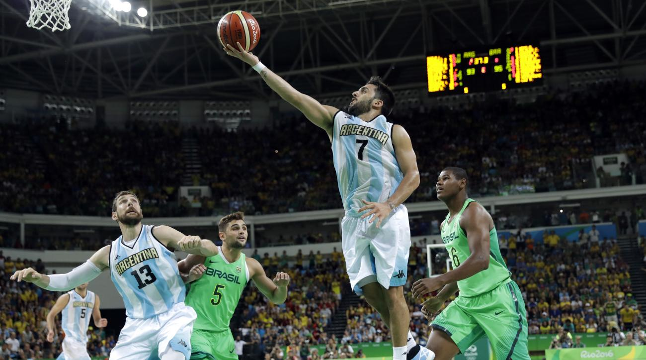 Argentina's Facundo Campazzo (7) drives to the basket past Brazil's Cristiano Felicio, right, during a basketball game at the 2016 Summer Olympics in Rio de Janeiro, Brazil, Saturday, Aug. 13, 2016. Argentina won 111-107 in double overtime. (AP Photo/Char