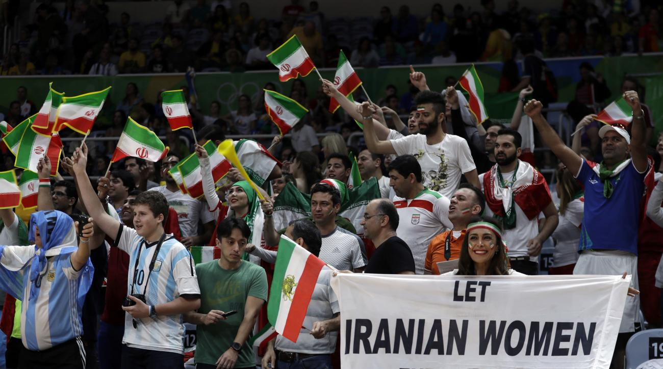 CORRECTS NAME TO DARYA SAFAI INSTEAD OF SARAI DARYA - Fans cheer and wave the flag of Iran as Darya Safai, right, holds a large sign protesting the fact that women have not been allowed to attend volleyball matches in Iran during a men's preliminary volle
