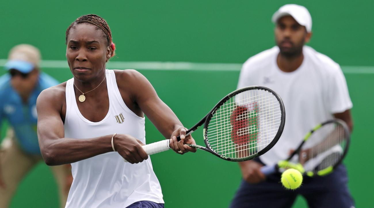 Venus Williams, left, misses a return against the Netherlands while playing a mixed doubles match with her partner Rajeev Ram, right, at the 2016 Summer Olympics in Rio de Janeiro, Brazil, Thursday, Aug. 11, 2016. (AP Photo/Charles Krupa)