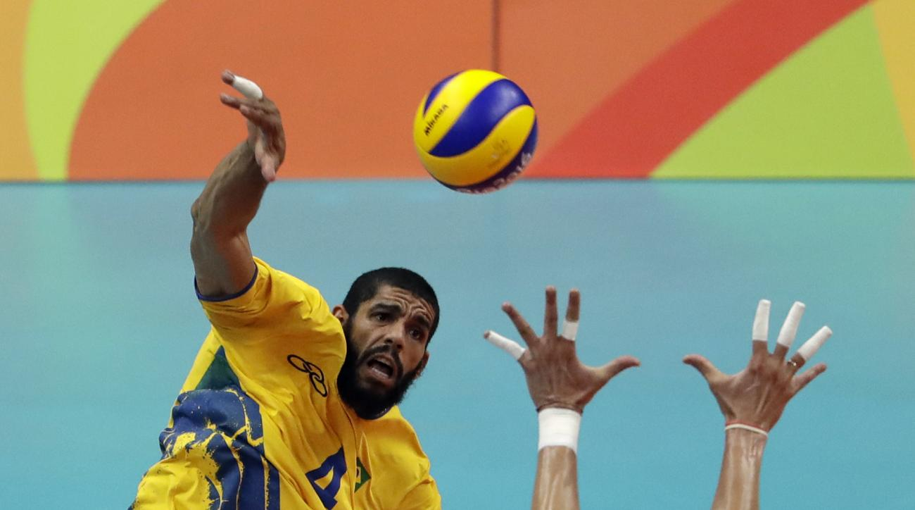 Brazil's Wallace de Souza, left, spikes the ball as Italy's Osmany Juantorena blocks during a men's preliminary volleyball match at the 2016 Summer Olympics in Rio de Janeiro, Brazil, Saturday, Aug. 13, 2016. (AP Photo/Matt Rourke)