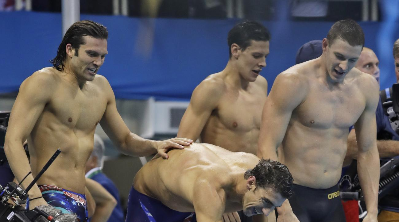 United States' Michael Phelps shakes hands with teammate United States Nathan Adrian after their team won the men's 4 x 100-meter medley relay final during the swimming competitions at the 2016 Summer Olympics, Saturday, Aug. 13, 2016, in Rio de Janeiro,