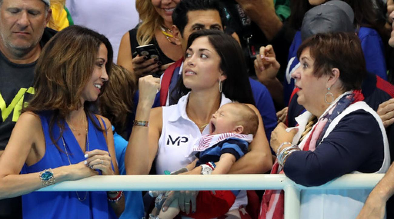Nicole Johnson, fiance of United States' Michael Phelps, holds their baby Boomer, as she stands along with Phelps' mother Debbie and sister during the men's 4 x 100-meter medley relay final during the swimming competitions at the 2016 Summer Olympics, Sat