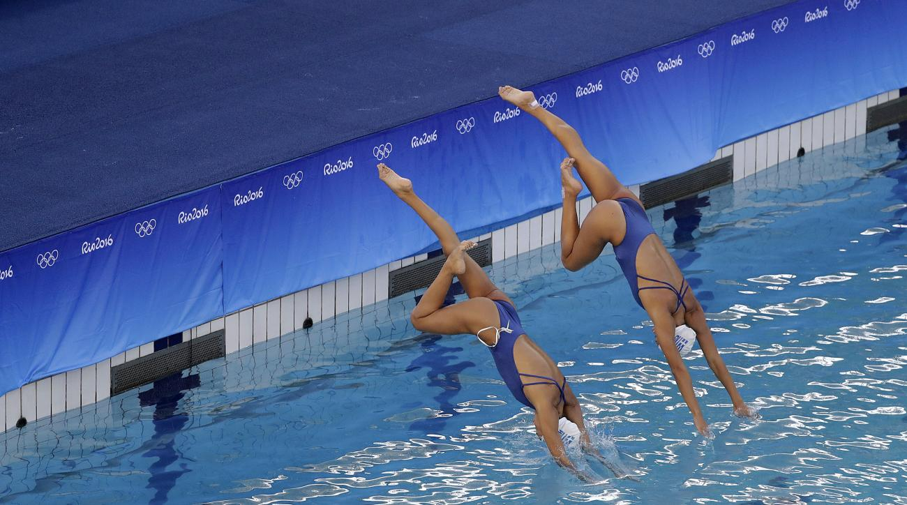 Greece's synchronized swimming duets team of Evangelia Papazoglou and Evangelia Platanioti dive into the pool in the Lenk Aquatic Center during a training session the morning after the pool went through a change in water, on Sunday, Aug. 14, 2016 in Rio d