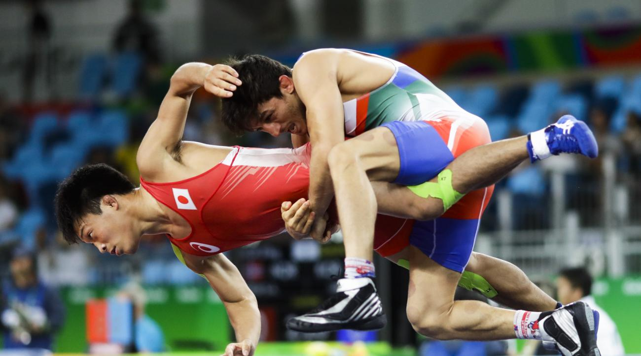 Japan's Shinobu Ota, red, competes against Iran's Hamid Mohammad Soryan during the during the men's Greco-Roman 59-kg competition at the 2016 Summer Olympics in Rio de Janeiro, Brazil, Sunday, Aug. 14, 2016. (AP Photo/Markus Schreiber)