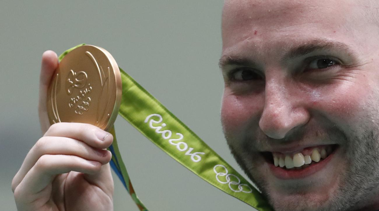 Niccolo Campriani of Italy shows off his gold medal during the victory ceremony for the men's 50-meter rifle 3 positions finals at the Olympic Shooting Center at the 2016 Summer Olympics in Rio de Janeiro, Brazil, Sunday, Aug. 14, 2016. (AP Photo/Hassan A