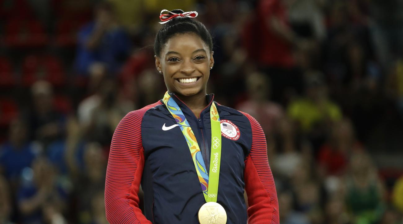 United States' Simone Biles smiles on the podium after winning vault gold during the artistic gymnastics women's apparatus final at the 2016 Summer Olympics in Rio de Janeiro, Brazil, Sunday, Aug. 14, 2016. (AP Photo/Dmitri Lovetsky)