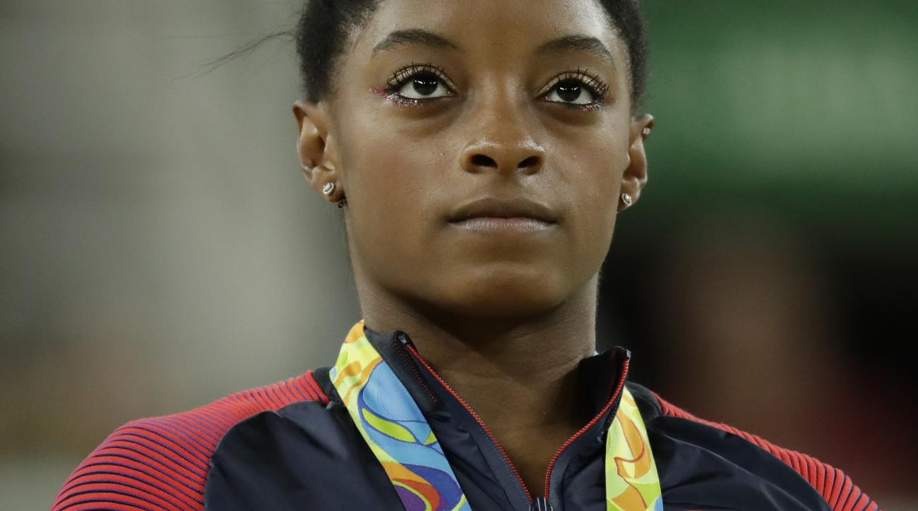 United States' Simone Biles, vault gold, stands for her national anthem during the artistic gymnastics women's apparatus final at the 2016 Summer Olympics in Rio de Janeiro, Brazil, Sunday, Aug. 14, 2016. (AP Photo/Dmitri Lovetsky)