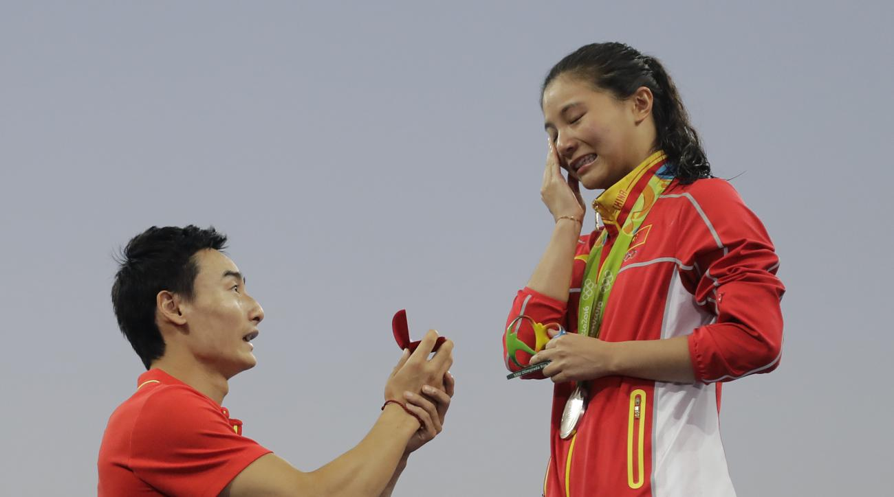 China's diver Qin Kai, left, proposes to silver medalist He Zhi of the women's 3-meter springboard diving finals in the Maria Lenk Aquatic Center at the 2016 Summer Olympics in Rio de Janeiro, Brazil, Sunday, Aug. 14, 2016. (AP Photo/Wong Maye-E)