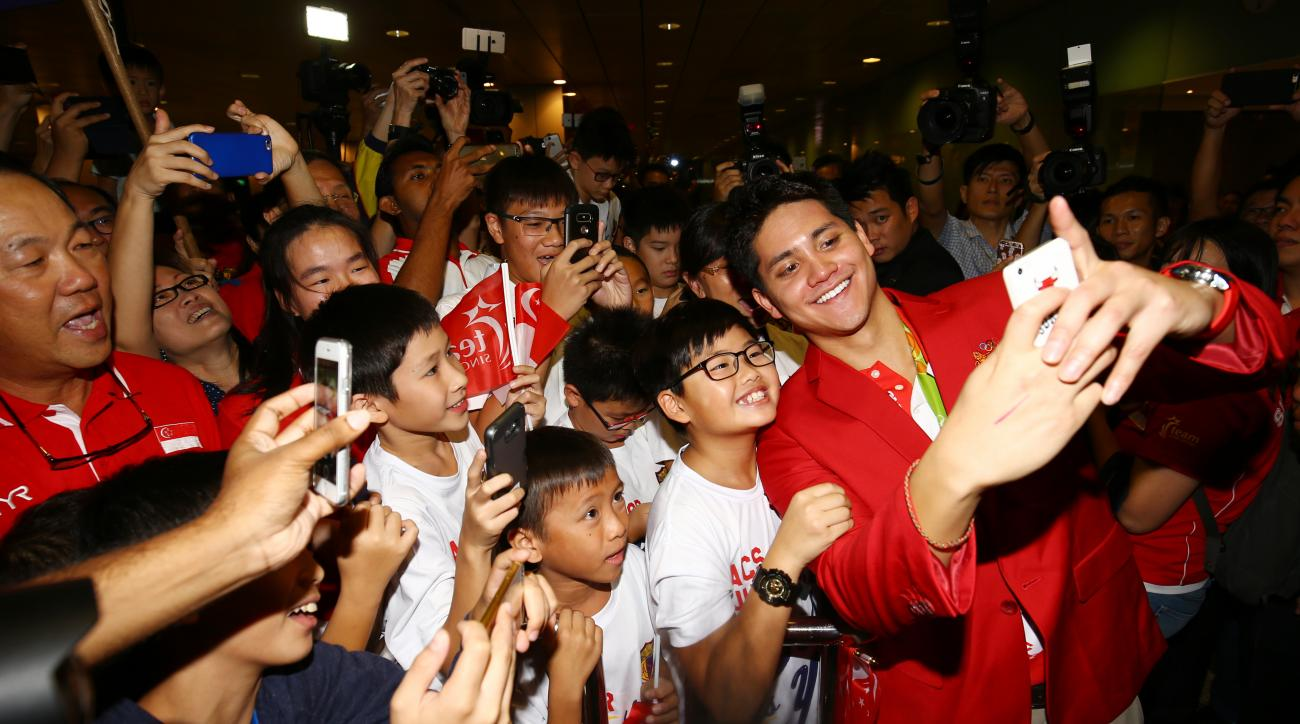 Singaporean swimmer Joseph Schooling, front right, poses for a photo with people at the Singapore Changi Airport in Singapore Monday, Aug. 15, 2016. Schooling won gold medal in the men's 100-meter butterfly and made history by winning the country's first