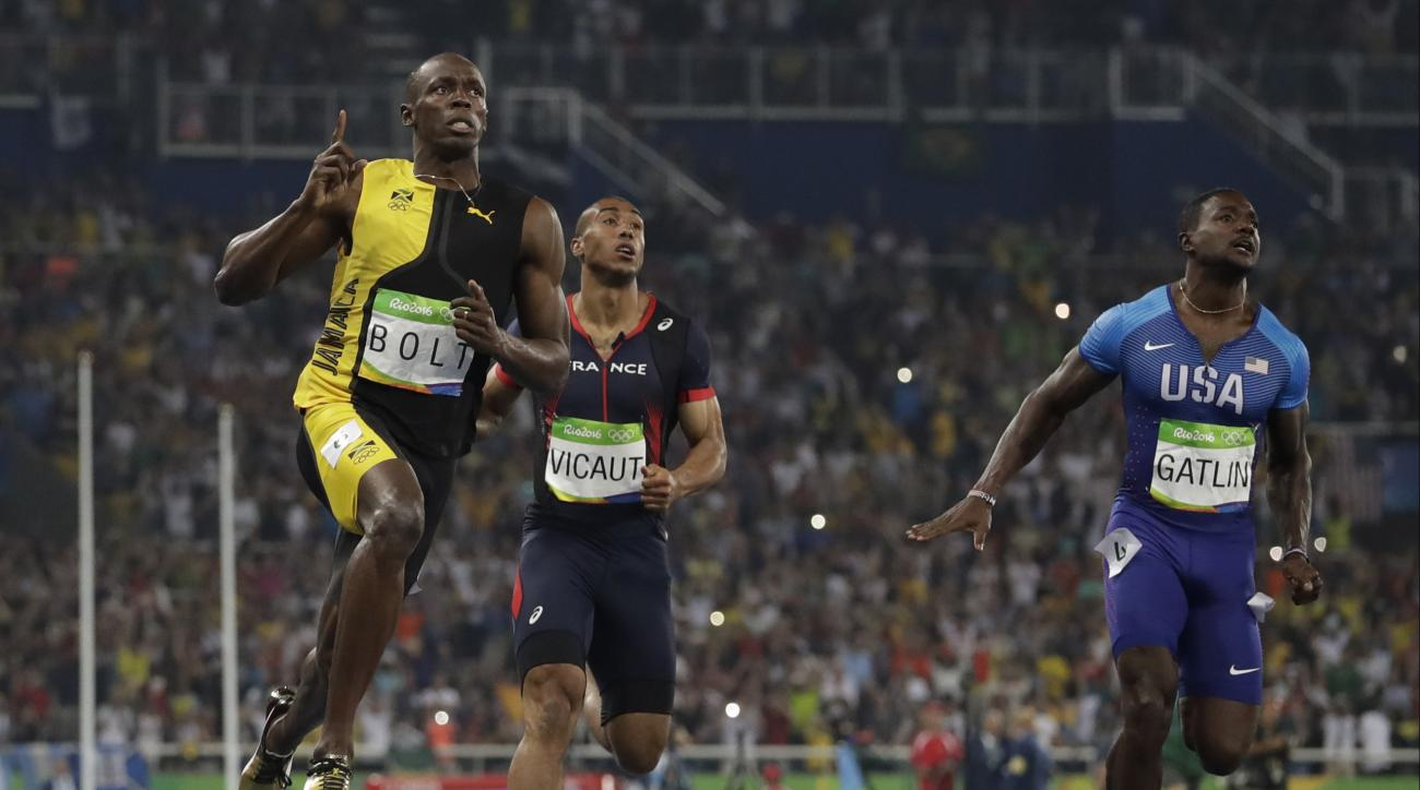 Jamaica's Usain Bolt, left, celebrates winning the men's 100-meter final during the athletics competitions of the 2016 Summer Olympics at the Olympic stadium in Rio de Janeiro, Brazil, Sunday, Aug. 14, 2016. (AP Photo/David J. Phillip)