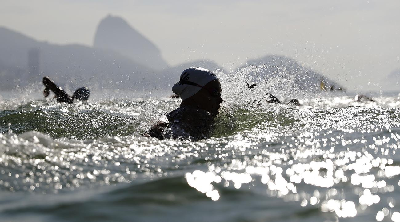 Sharon van Rouwendaal, of the Netherlands, enters the water with fellow competitors as they make their way to the starting line off the shore of Copacabana beach for the women's marathon swimming event at the 2016 Summer Olympics in Rio de Janeiro, Brazil