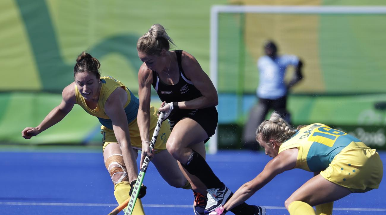 New Zealand's Gemma Flynn, fights for the ball with Australia's Karri McMahon, left, and Australia's Jane Claxton, right, during a women's field hockey quarterfinal match at 2016 Summer Olympics in Rio de Janeiro, Brazil, Monday, Aug. 15, 2016. (AP Photo/