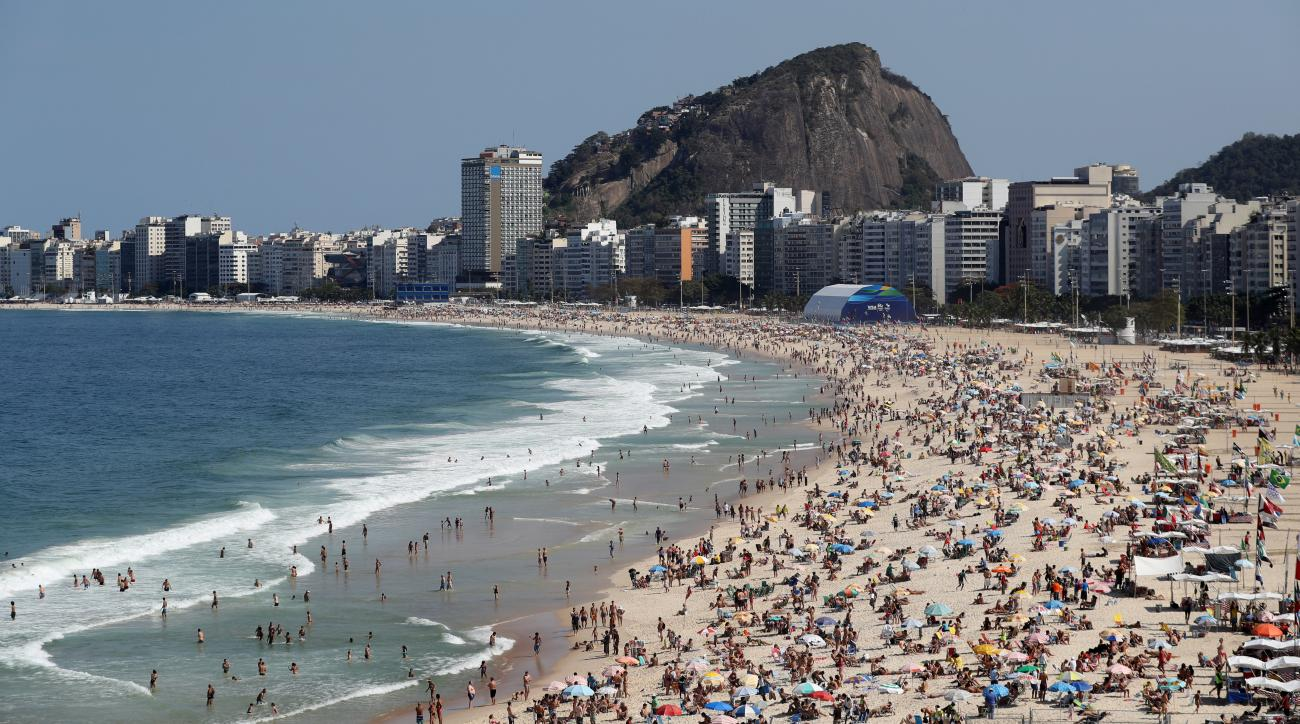 FILE - In this Aug. 5, 2016 file photo, people enjoy a sunny day on Copacabana beach prior to the 2016 Summer Olympics in Rio de Janeiro, Brazil. Its a given that Olympic athletes have chiseled muscles, but tourists in Rio for the games cant help but noti