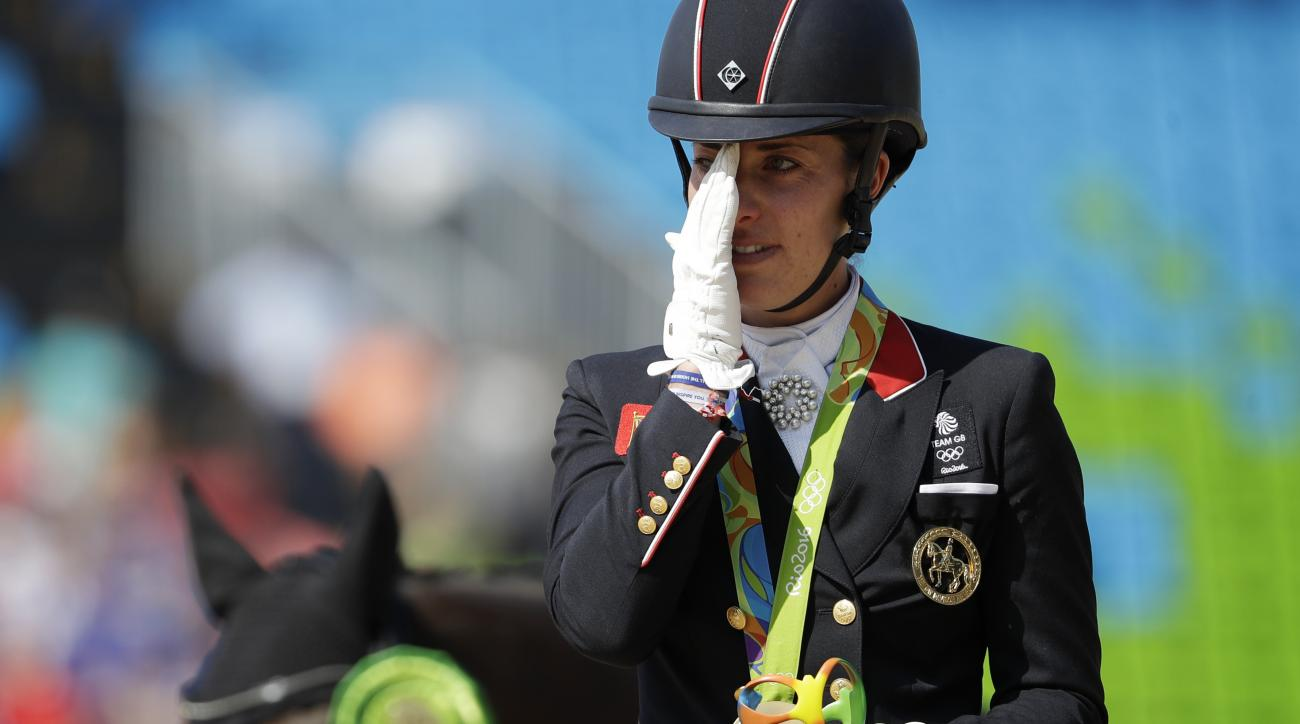 Britain's Charlotte Dujardin reacts on the podium after winning a gold medal in the equestrian dressage individual competition at the 2016 Summer Olympics in Rio de Janeiro, Brazil, Monday, Aug. 15, 2016. (AP Photo/John Locher)