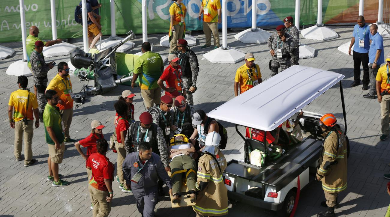 An injured woman is taken away on a backboard after being struck by an overhead television camera, laying top left, that fell from the wires suspending it over Olympic Park during the Summer Games in Rio de Janeiro, Brazil, Monday, Aug. 15, 2016. A witnes