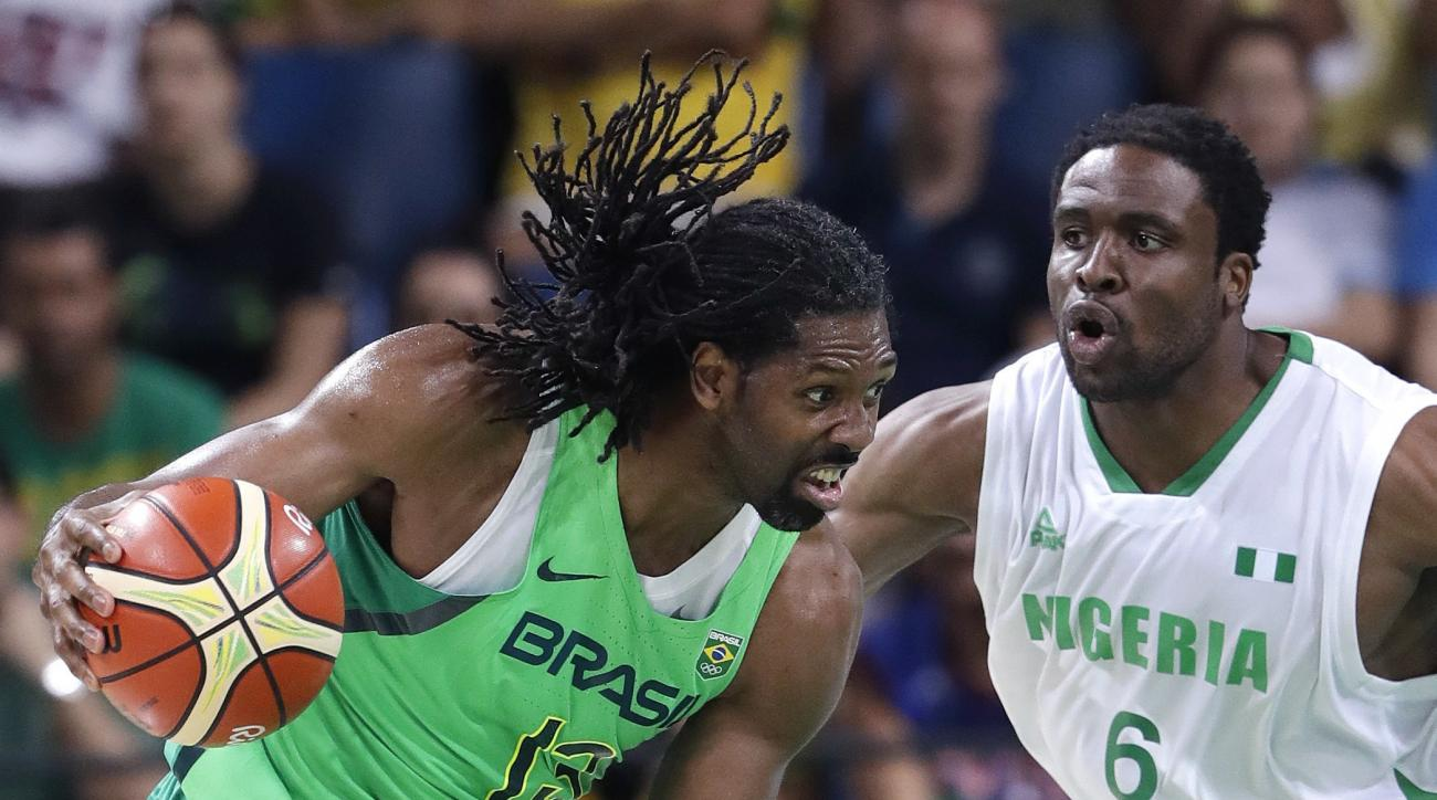 Brazil's Nene Hilario (13) drives around Nigeria's Ike Diogu (6) during a men's basketball game at the 2016 Summer Olympics in Rio de Janeiro, Brazil, Monday, Aug. 15, 2016. (AP Photo/Eric Gay)