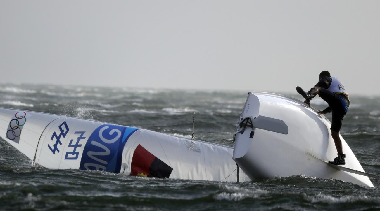 A member of the Angola crew of the 470 men category try to right his boat as a sudden strong wind hit the Guanabara bay forcing the postponing of the scheduled sailing races during the 2016 Summer Olympics in Rio de Janeiro, Brazil, Monday, Aug. 15, 2016.