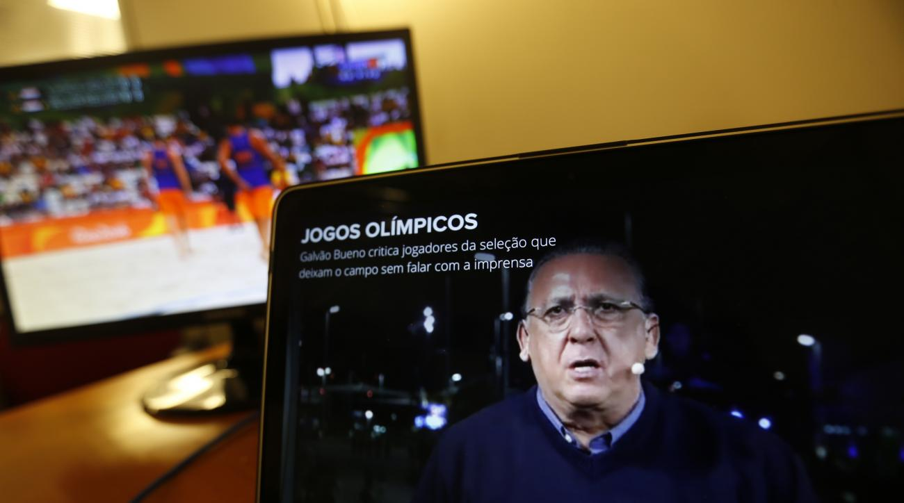 Carlos Eduardo dos Santos Galvao Bueno, chief sports commentator for Globo, is seen on a screen in Rio de Janeiro, Brazil, Monday, Aug. 15, 2016. When a BBC announcer suggested that the Brazilian broadcaster needed to shut up at the start of a swimming ra