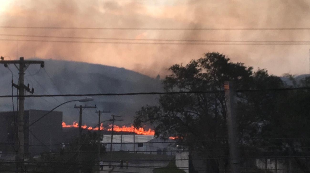 A fire burns roughly 10 miles from the Olympic field hockey venue during the 2016 Summer Olympics in Rio de Janeiro, Brazil, Monday, Aug. 15, 2016. High winds blew smoke and ash onto the playing surfaces before the evening session, which included two matc