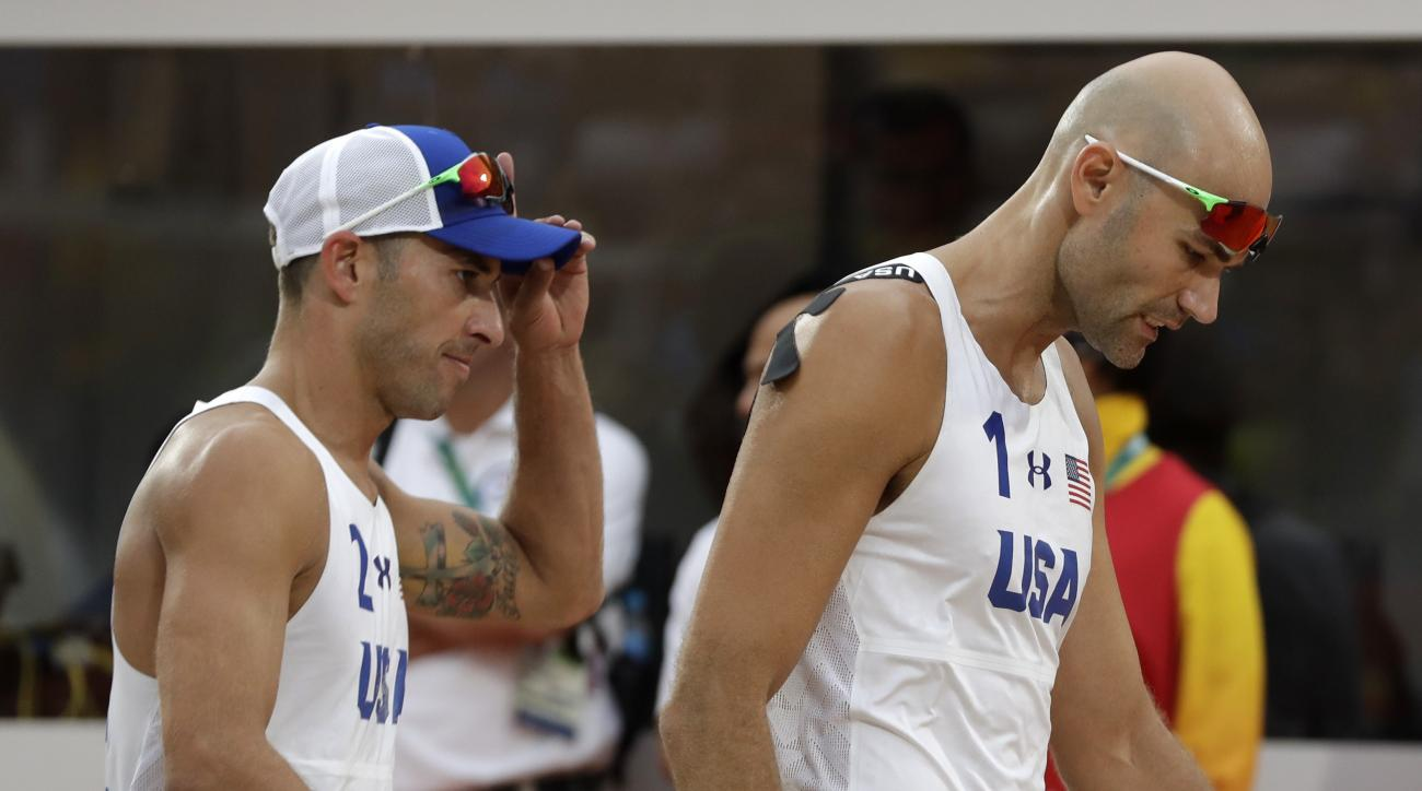 United States' Phil Dalhausser, right, and Nicholas Lucena, left, leave the pitch after loosing to Brazil in a men's beach volleyball quarterfinal match at the 2016 Summer Olympics in Rio de Janeiro, Brazil, Monday, Aug. 15, 2016. (AP Photo/Petr David Jos