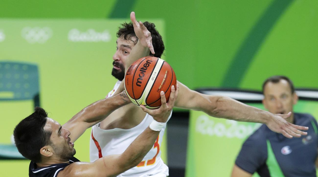Argentina's Facundo Campazzo, left, is fouled by Spain's Sergio Llull while driving to the basket during a basketball game at the 2016 Summer Olympics in Rio de Janeiro, Brazil, Monday, Aug. 15, 2016. (AP Photo/Charlie Neibergall)