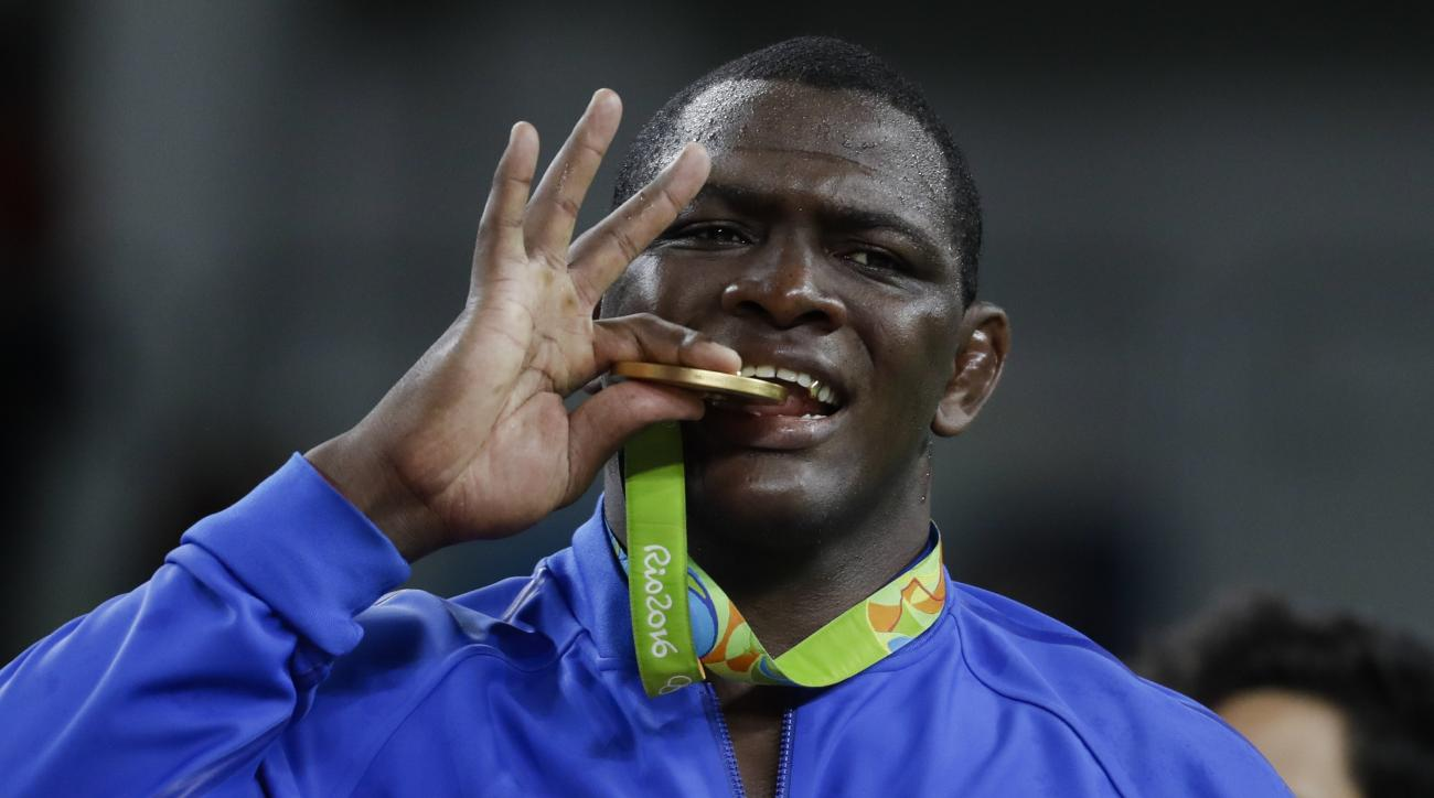 Gold medalist Cuba's Mijain Lopez Nunez celebrates with the medal during the winners ceremony for the men's wrestling Greco-Roman 130-kg competition at the 2016 Summer Olympics in Rio de Janeiro, Brazil, Monday, Aug. 15, 2016. (AP Photo/Markus Schreiber)
