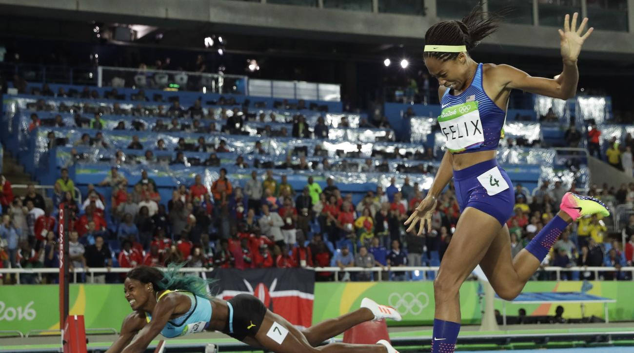 Bahamas' Shaunae Miller falls over the finish line to win gold ahead of United States' Allyson Felix, right, in the women's 400-meter final during the athletics competitions of the 2016 Summer Olympics at the Olympic stadium in Rio de Janeiro, Brazil, Mon