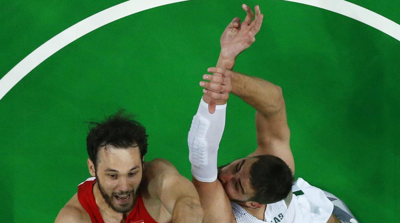Croatia's Miro Bilan, left, shoots over Lithuania's Jonas Valanciunas, right, during a basketball game at the 2016 Summer Olympics in Rio de Janeiro, Brazil, Monday, Aug. 15, 2016. (Jim Young/Pool Photo via AP)