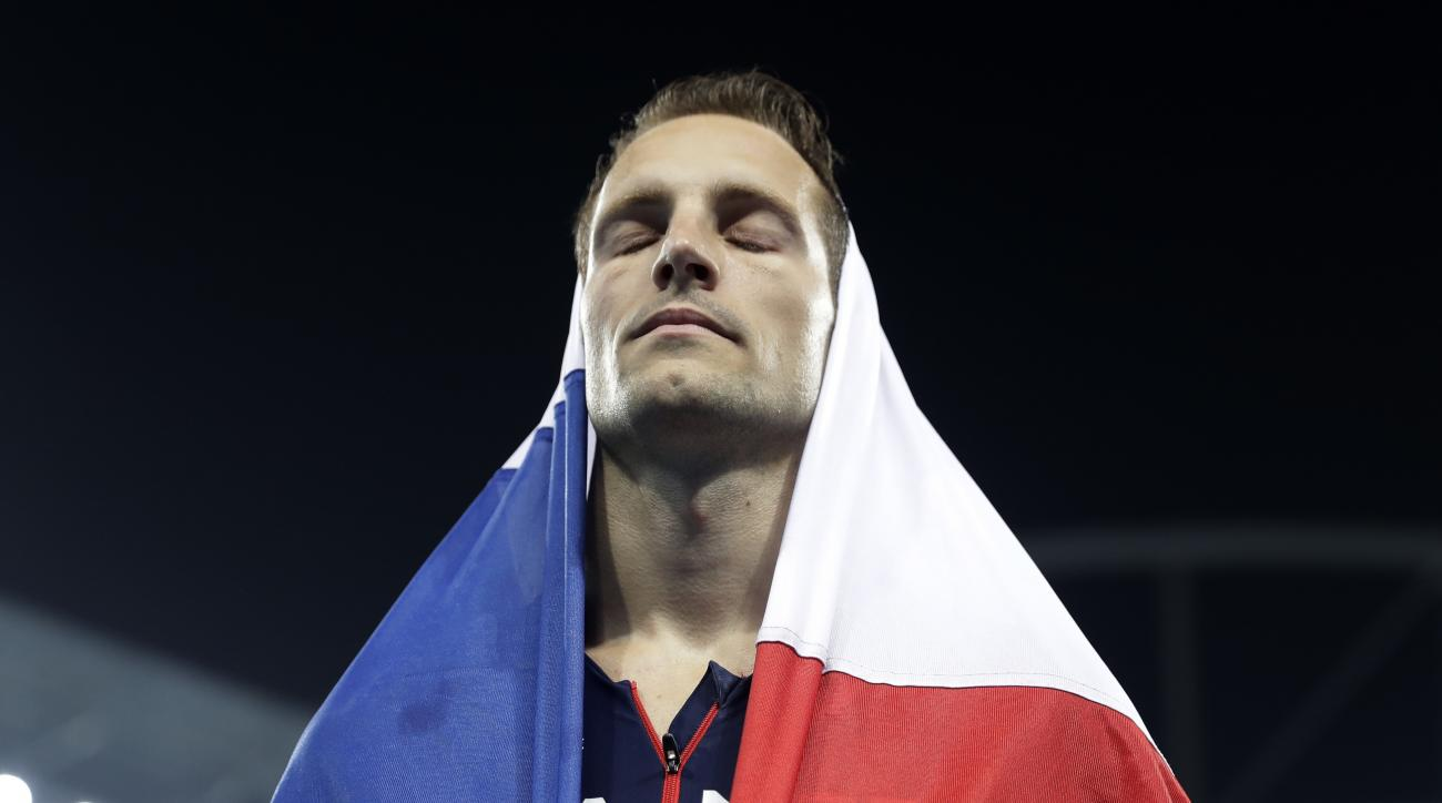 France's Renaud Lavillenie is covered in a French flag as he leaves the stadium after taking the silver medal in the men's pole vault final during the athletics competitions of the 2016 Summer Olympics at the Olympic stadium in Rio de Janeiro, Brazil, Tue