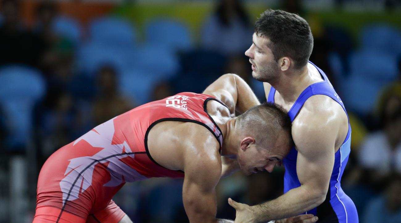 Germany's Frank Staebler, red, competes against Serbia's Davor Stefanek during the during the men's wrestling Greco-Roman 66-kg competition at the 2016 Summer Olympics in Rio de Janeiro, Brazil, Tuesday, Aug. 16, 2016. (AP Photo/Markus Schreiber)