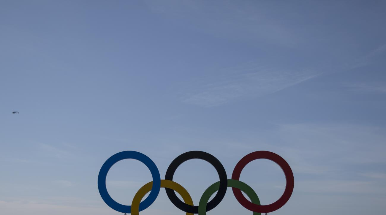 Spectators stand behind the Olympic rings after men's marathon event at the 2016 Summer Olympics in Rio de Janeiro, Brazil, Tuesday, Aug. 16, 2016. (AP Photo/Felipe Dana)
