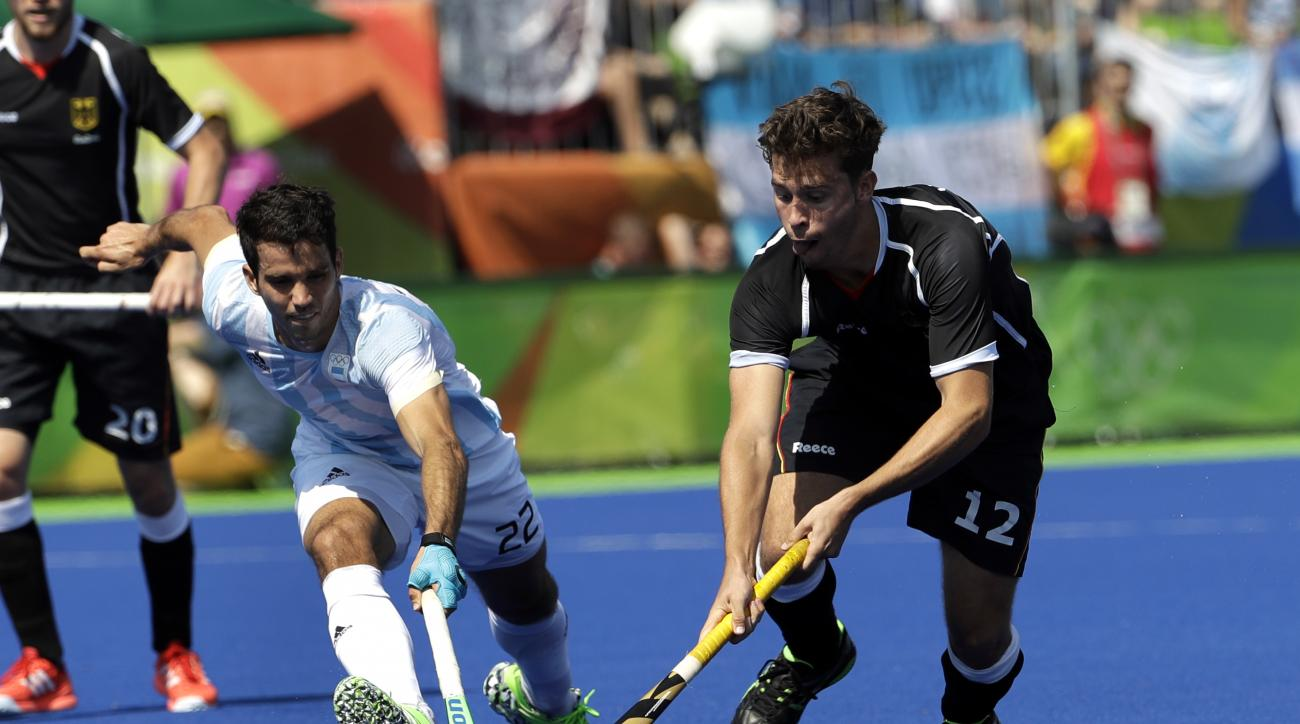 Germany's Timm Herzbruch, right, fights for the ball with Argentina's Matias Rey, left, during a men's field hockey semifinal match at 2016 Summer Olympics in Rio de Janeiro, Brazil, Tuesday, Aug. 16, 2016. (AP Photo/Hussein Malla)