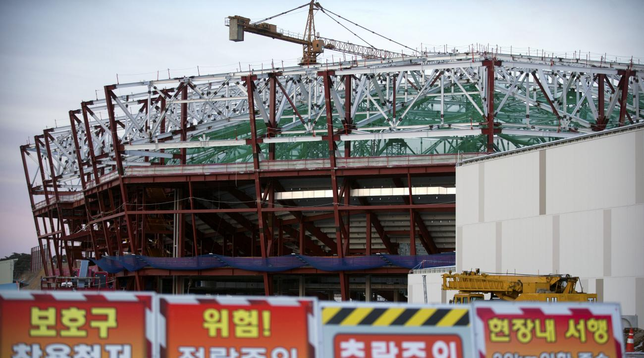 FILE - In this Feb. 5, 2016 file photo, caution signs stand outside a hockey arena under construction in Gangneung, South Korea, during a media tour of venues ahead of a World Cup skiing event that will be the first test event for the 2018 Olympic Games.