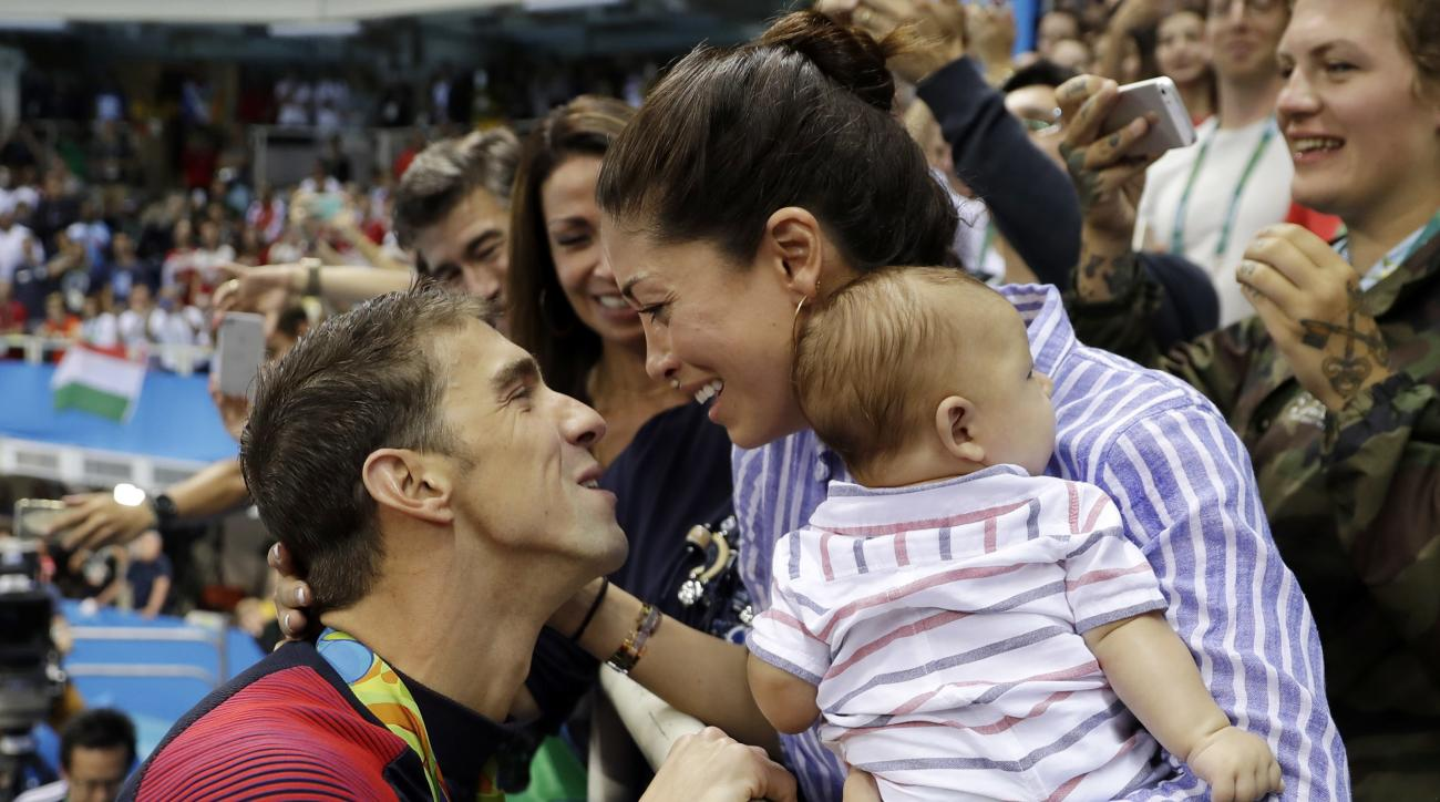 FILE - In this Aug. 9, 2016, file photo, United States' Michael Phelps celebrates winning his gold medal in the men's 200-meter butterfly with his fiance Nicole Johnson and baby Boomer during the swimming competitions at the 2016 Summer Olympics, in Rio d
