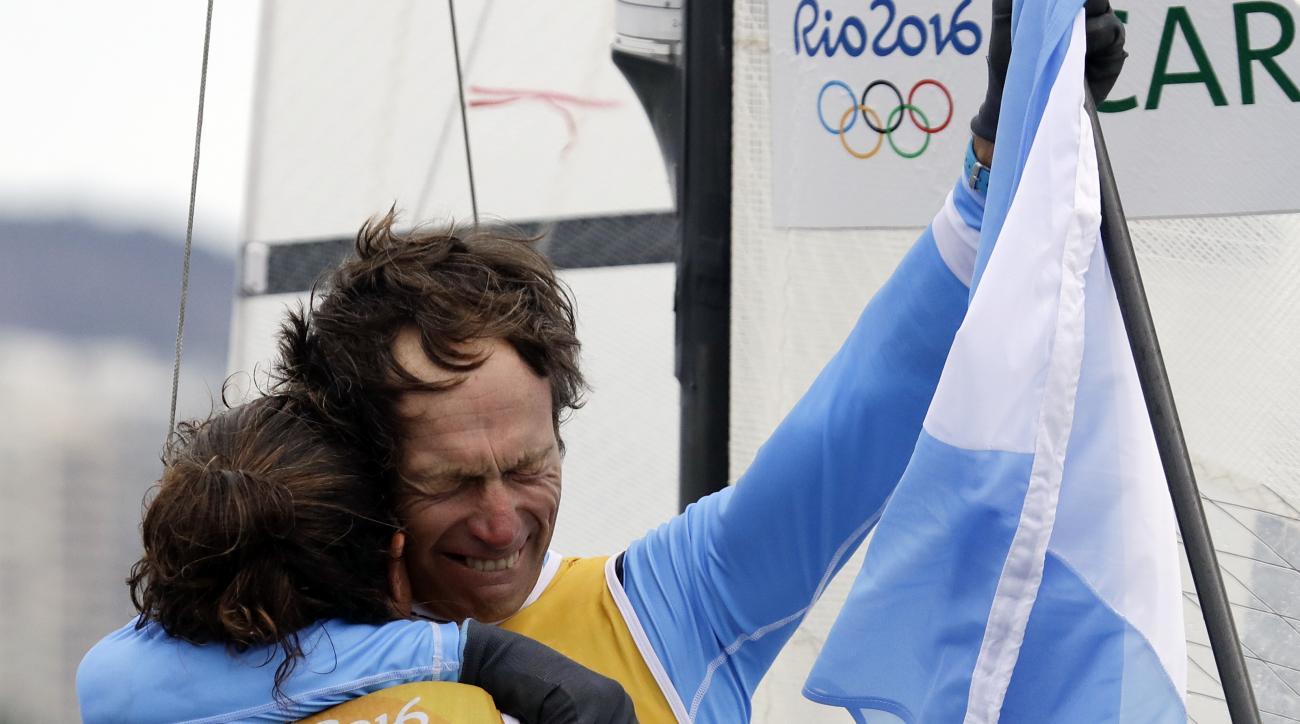 First placed Argentina's Santiago Lange, right, hugs Cecilia Carranza Saroli at the end of the Nacra 17 Mixed Medal Race during the 2016 Summer Olympics in Rio de Janeiro, Brazil, Tuesday, Aug. 16, 2016. (AP Photo/Gregorio Borgia)
