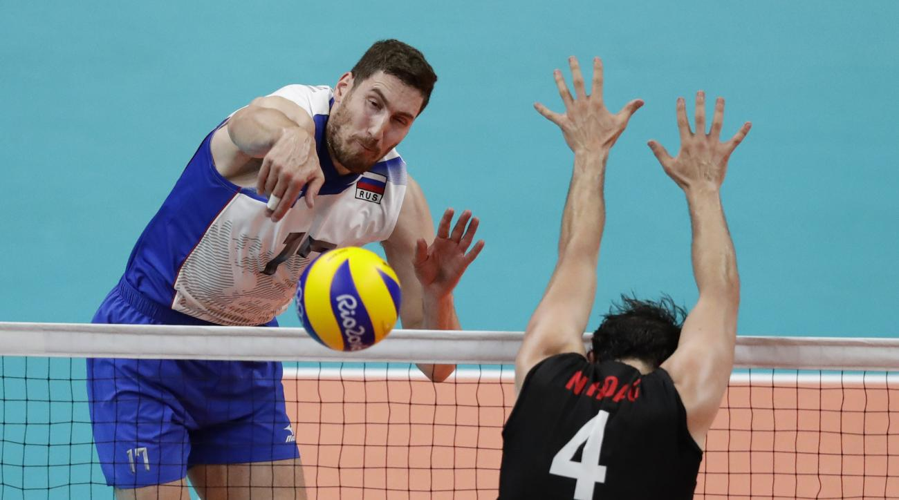 Russia's Maxim Mikhaylov spikes the ball Canada's Nicholas Hoag in a men's quarterfinal volleyball match at the 2016 Summer Olympics in Rio de Janeiro, Brazil, Wednesday, Aug. 17, 2016. (AP Photo/Robert F. Bukaty)