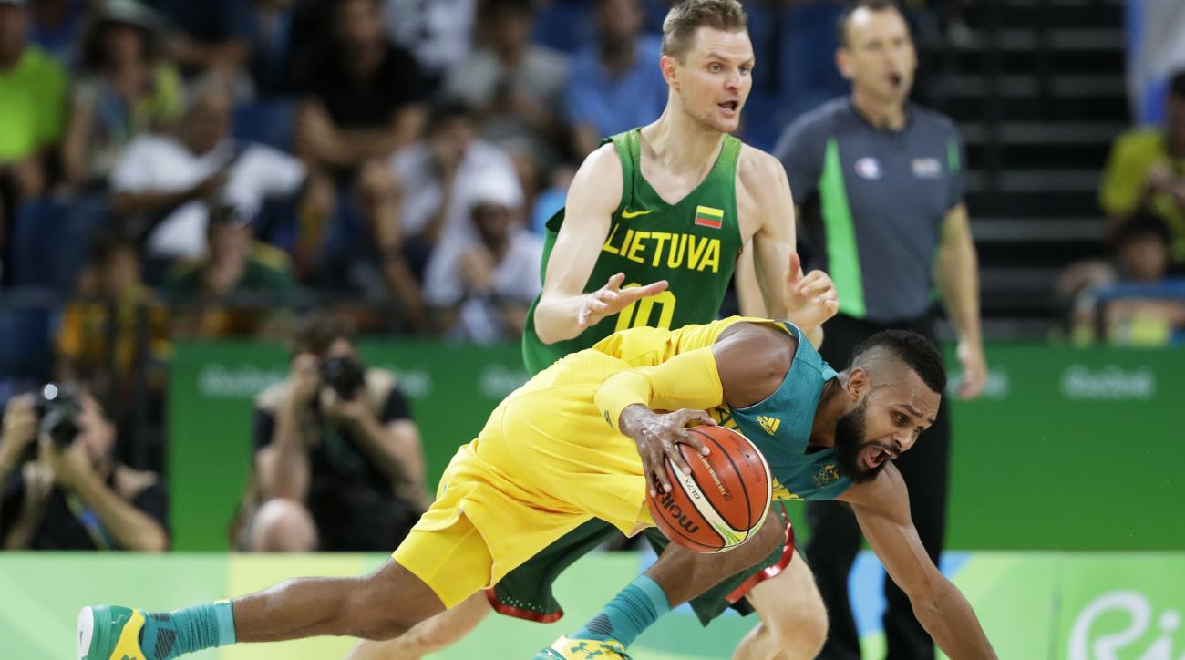 Australia's Patty Mills drives past Lithuania's Renaldas Seibutis (10) during a quarterfinal round basketball game at the 2016 Summer Olympics in Rio de Janeiro, Brazil, Wednesday, Aug. 17, 2016. (AP Photo/Charlie Neibergall)