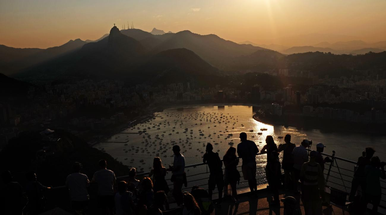 The Christ the Redeemer statue stands in the distance as visitors look out from atop Sugarloaf Mountain during the 2016 Summer Olympics in Rio de Janeiro, Brazil, Wednesday, Aug. 17, 2016. (AP Photo/David Goldman)