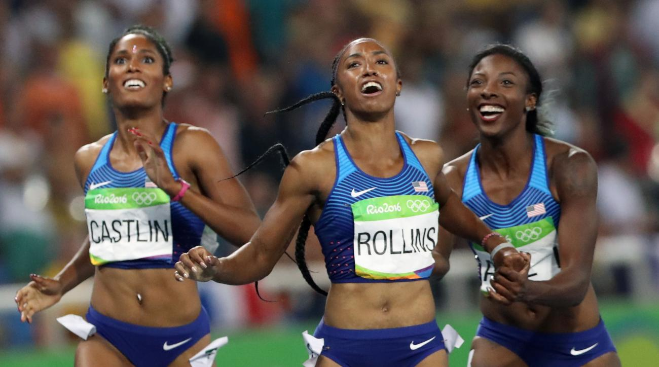 Gold medal winner Brianna Rollins, center, silver medal winner, Nia Ali, right, and bronze medal winner Kristi Castlin, all from the United States, pose with their country's flag after the 100-meter hurdles final,during the athletics competitions of the 2